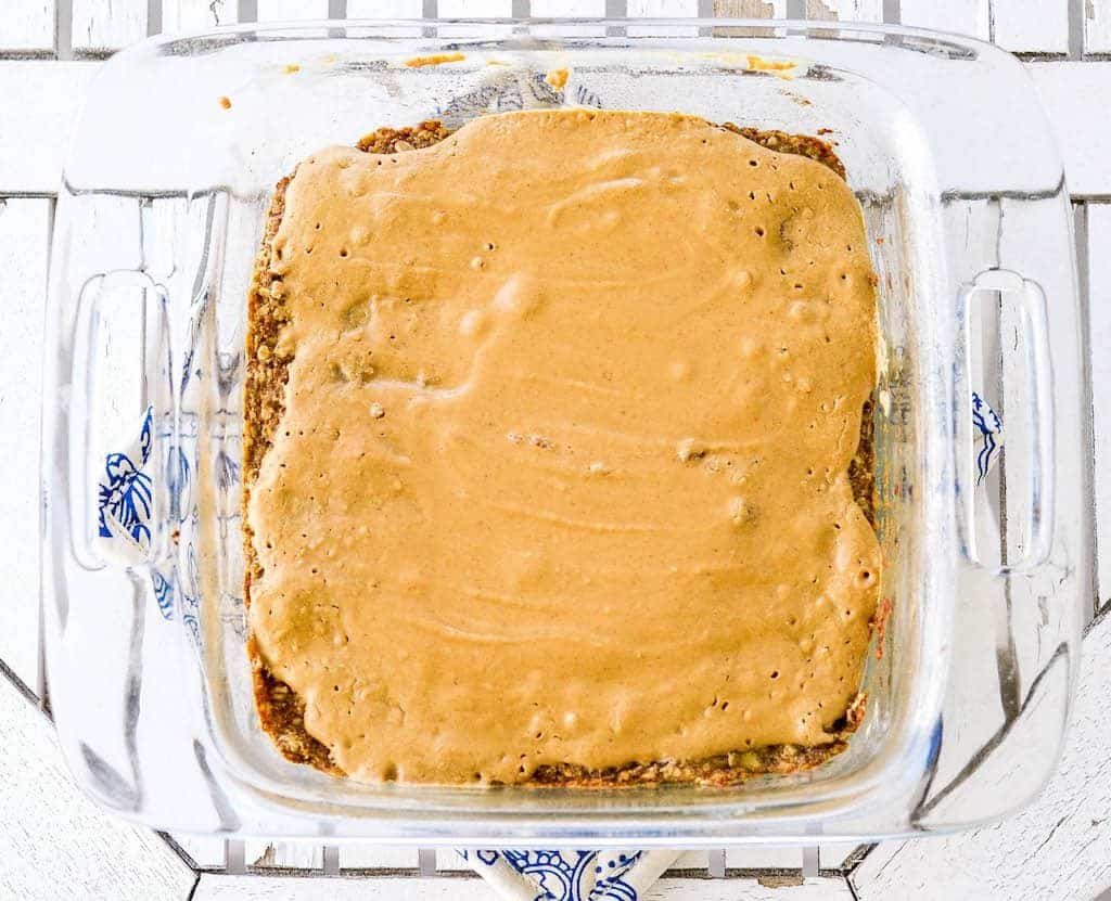 Overhead view of Peanut Butter Oatmeal Breakfast Bars in an eight inch square baking pan after being baked before cutting