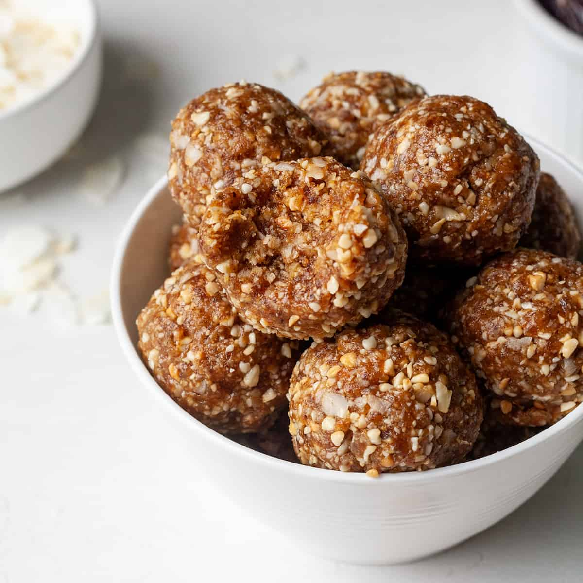 a bowl of coconut date balls, the top one has a bite taken out of it