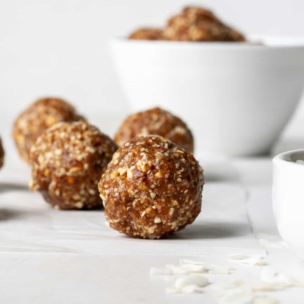 four Cashew Coconut Date Balls in front of a bowl of date balls.