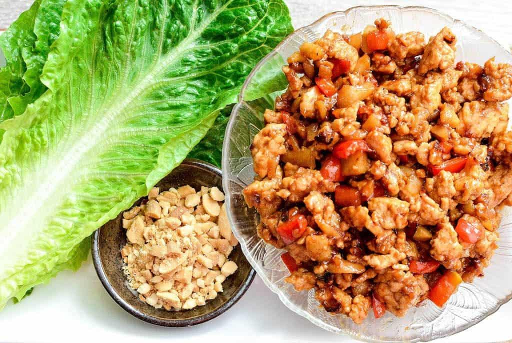 Overhead view of a bowl Asian Chicken Lettuce Wraps filling on a platter with fresh lettuce and a small bowl of crushed peanuts.