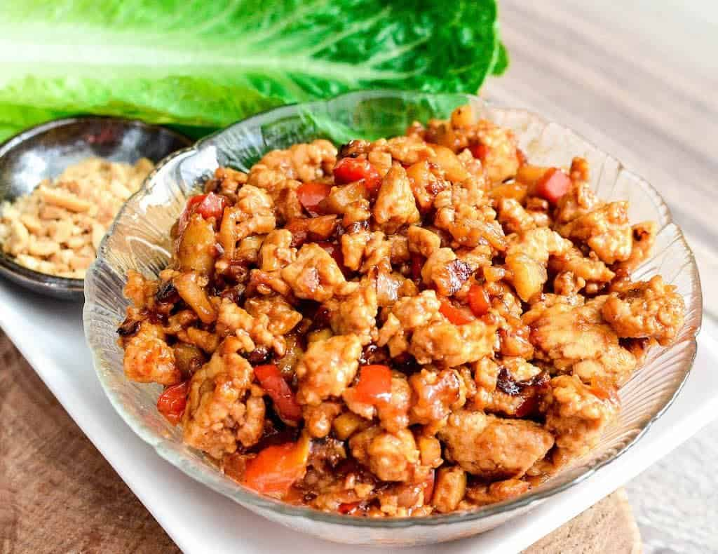 Front view of a bowl of Asian Chicken Lettuce Wraps filling on a platter with fresh lettuce and a bowl of crushed peanuts in the background.