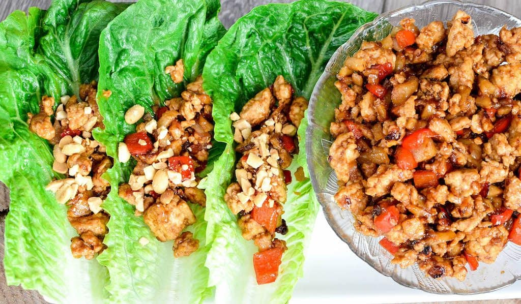 Overhead view of three asian lettuce wraps on a platter sprinkled with peanuts with the bowl of lettuce wrap filling on the platter.