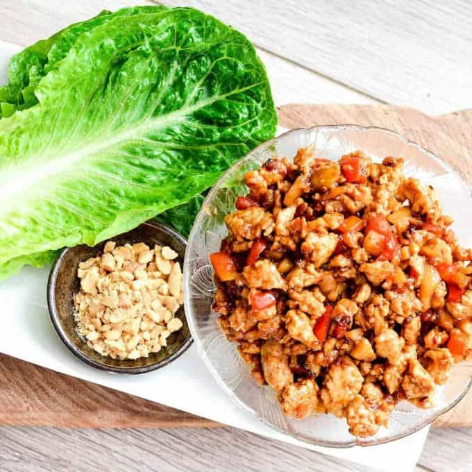 Overhead picture of asian chicken lettuce wrap filling in a bowl on a platter with fresh lettuce and crushed peanuts.