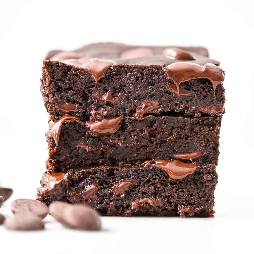 front view of a stack of three Black Bean Brownies with melty chocolate chips