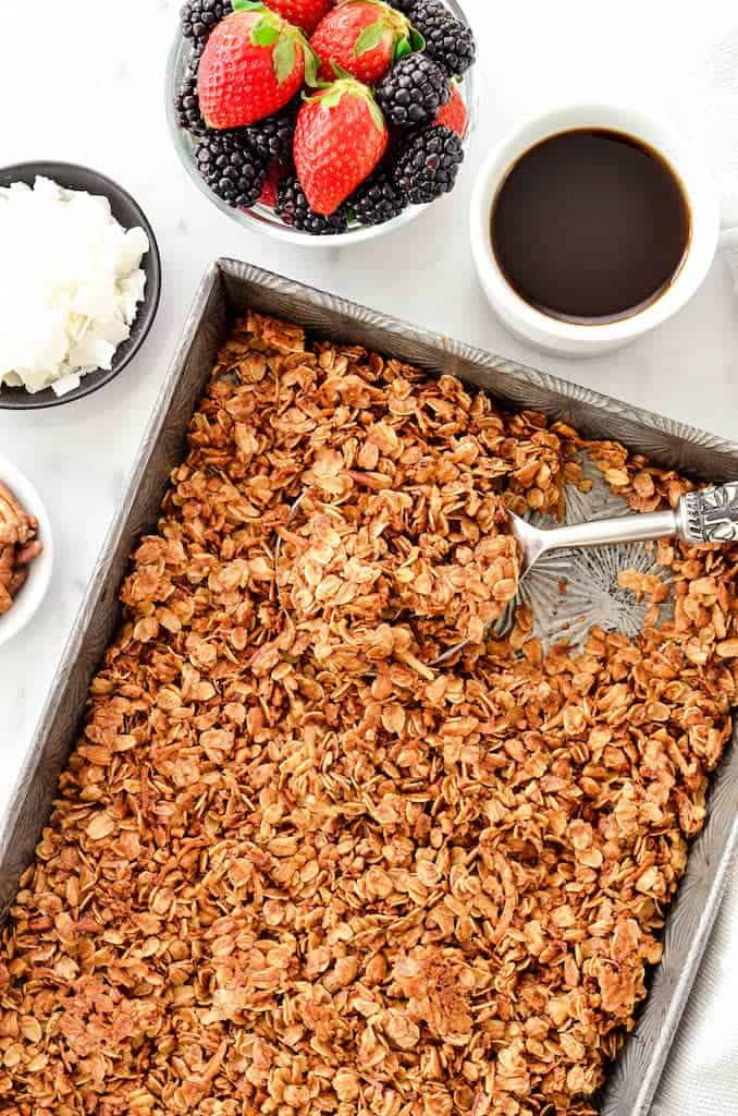 Overhead view of a baking pan with Healthy Granola being scooped out with a spoon