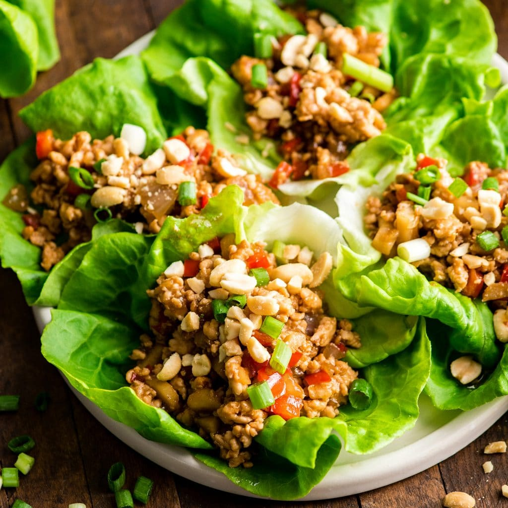 front view of four Asian Chicken Lettuce wraps on a plate with peanuts sprinkled on top