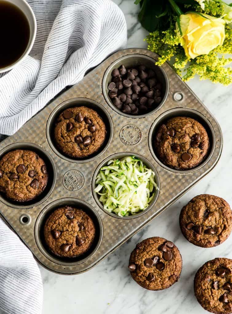Overhead view of a muffin tin with baked Paleo Zucchini Banana Muffins in it and three outside of it