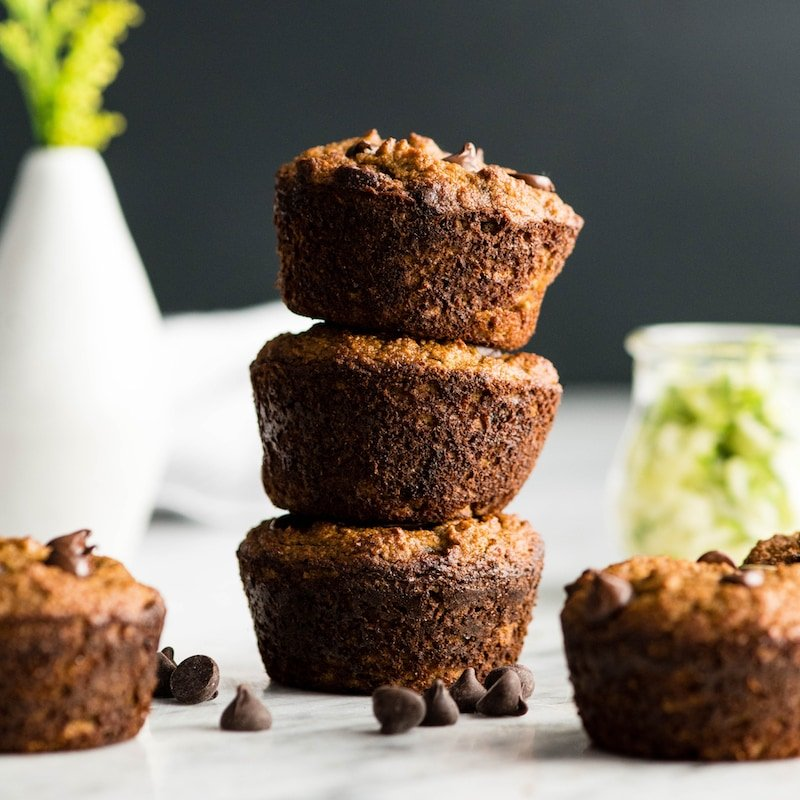 Front view of three Paleo Zucchini Banana Muffins stacked on top of each other with two muffins next to the stack