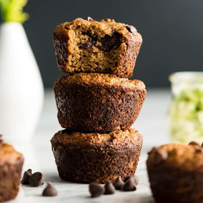 Front view of three Paleo Zucchini Banana Muffins stacked on each other, the top one has a bite taken out of it