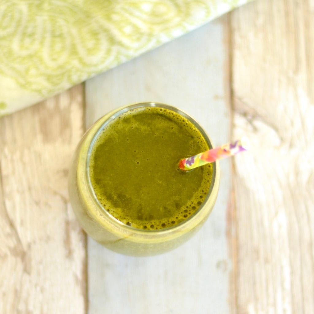overhead view of a glass with Chocolate Peanut Butter Green Smoothie and a straw
