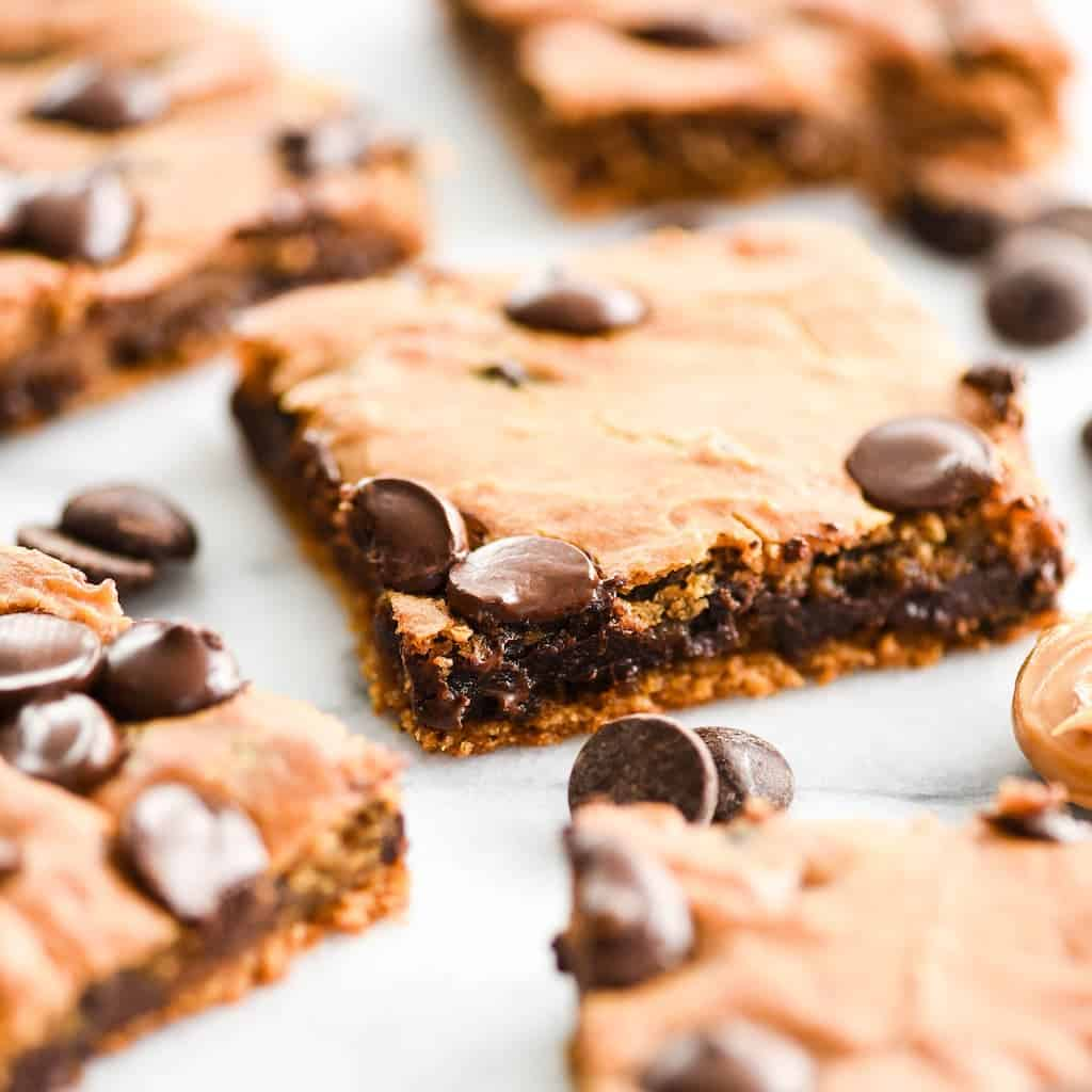 Angled front shot of one healthy peanut butter blondie surrounded by 4 other healthy peanut butter blondies, chocolate chips and a spoon full of peanut butter