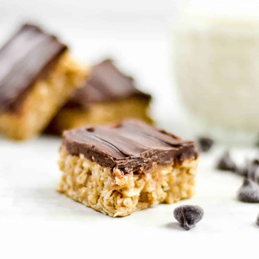 Front view of one No-Bake Chocolate Peanut Butter Coconut Bar with two stacked in the background