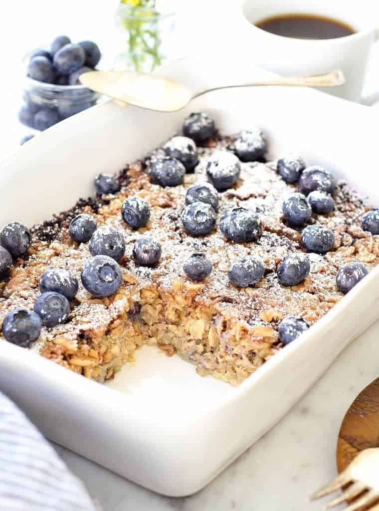 Side view of of blueberry baked oatmeal in a rectangular white baking dish with one piece cut out surrounded by flowers, coffee and extra blueberries