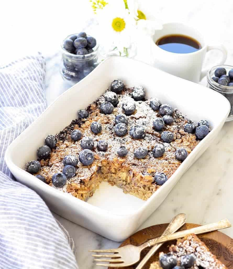 Side view of of blueberry baked oatmeal with one piece cut out in a rectangular white baking dish surrounded by flowers, coffee and extra blueberries