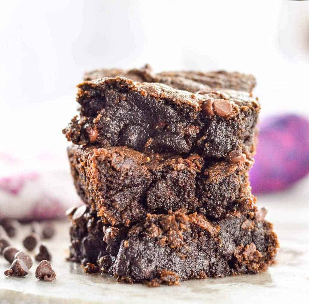 A front view of a stack of 3 goodey fudgy paleo brownies