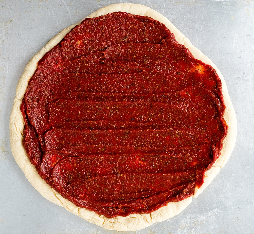 Overhead view of Easy Homemade Pizza Sauce recipe spread on a homemade pizza crust before toppings are added
