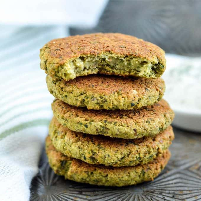 Front view of a stack of 5 healthy gluten-free vegan baked falafel, the top one has a bite taken out of it