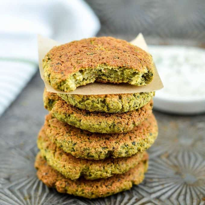 front view of a stack of 6 healthy vegan baked falafel, the top one has a bite taken out of it.