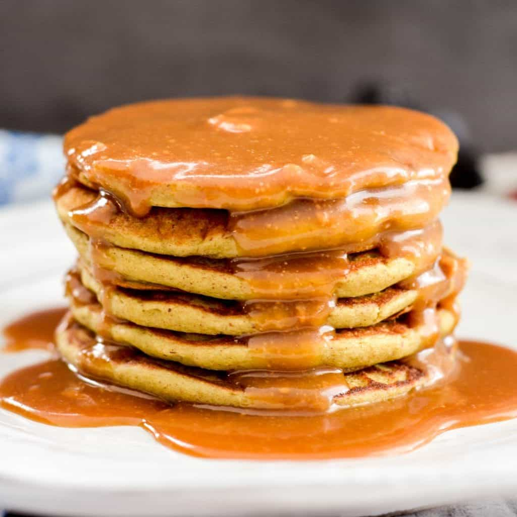 Front view of a stack of six Zucchini Banana Pancakes with maple syrup dripping down the top and sides