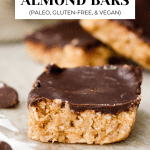 3 Coconut Almond Bars with chocolate and coconut pieces next to it.