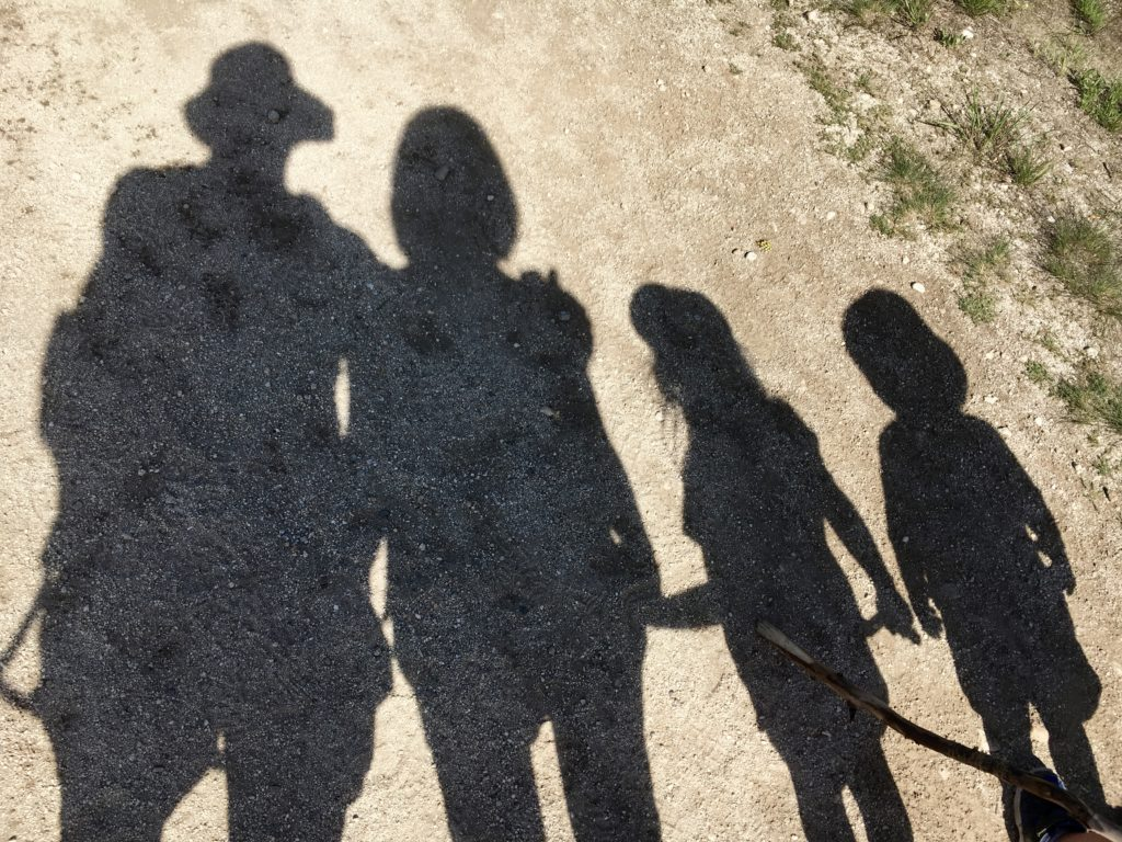 Picture of a a shadow of a family of five hiking in the complete guide to hiking with kids