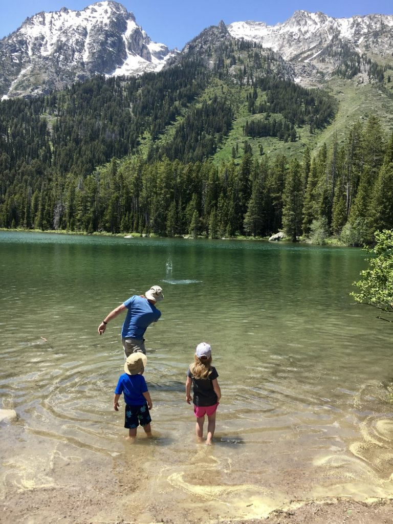 Family skipping rocks in a lake in the mountains in The Complete Guide to Hiking with Kids