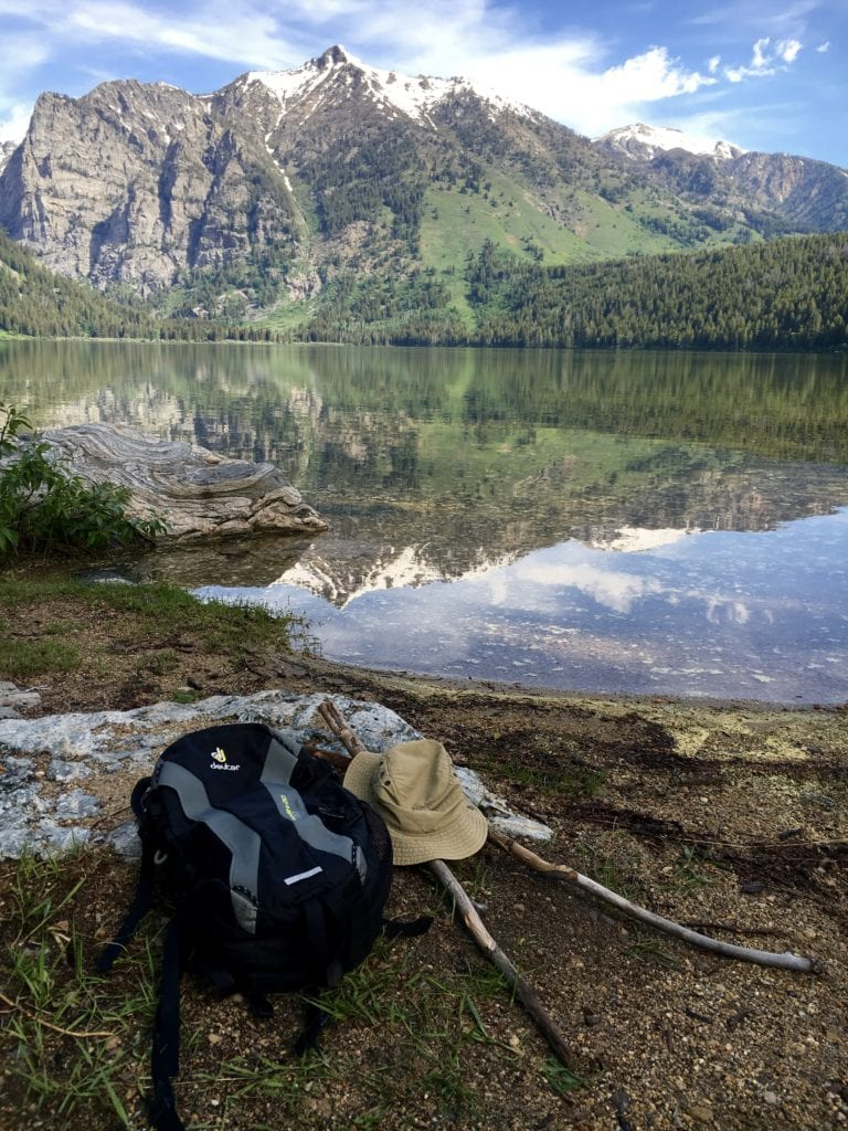 A photo of a backpack, hiking stick and hat laying near a lake in the mountains in The Complete Guide to Hiking with Kids