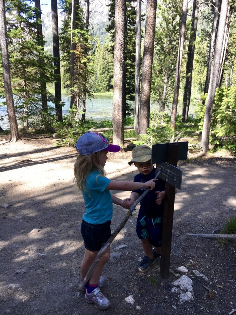 Two kids reading a trail sign in The Complete Guide to Hiking with Kids