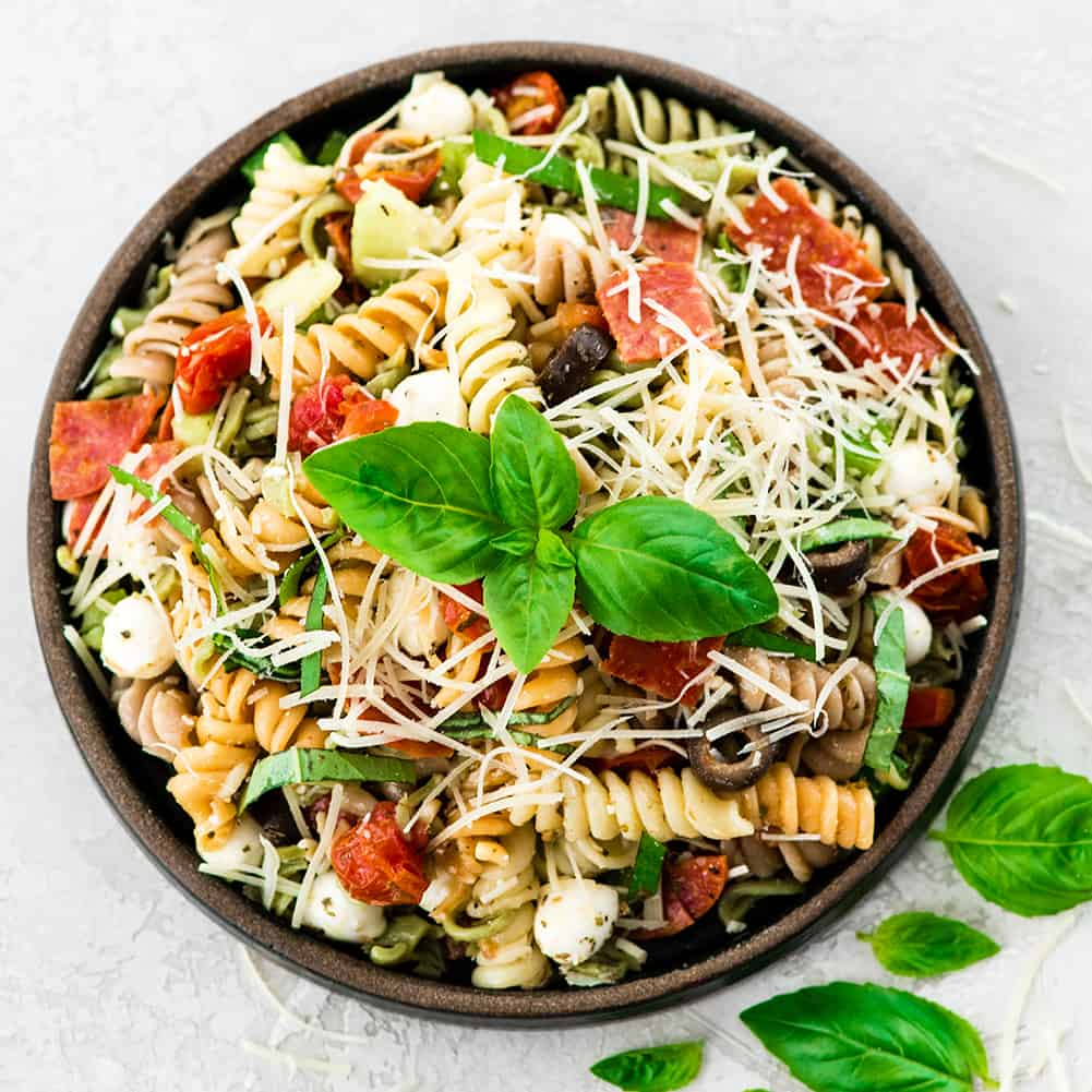 overhead view of Best Pasta Salad Recipe with Homemade Dressing on a plate garnished with fresh basil and Parmesan cheese