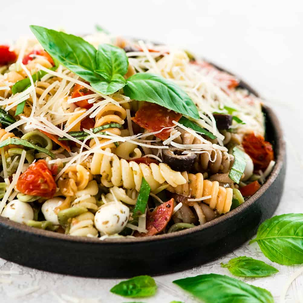 up close front view of Best Pasta Salad Recipe with Homemade Dressing on a plate garnished with fresh basil