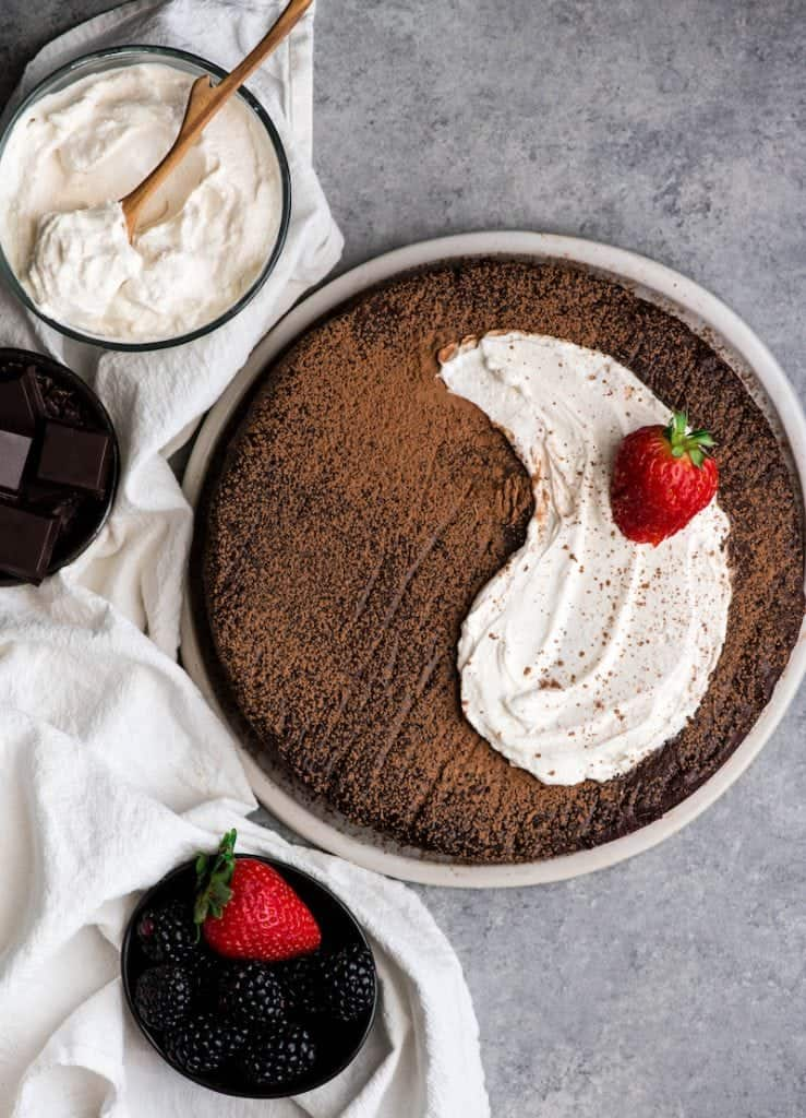 Overhead View Of A WholeBest Flourless Chocolate Cake On Plate With Whipped Cream And