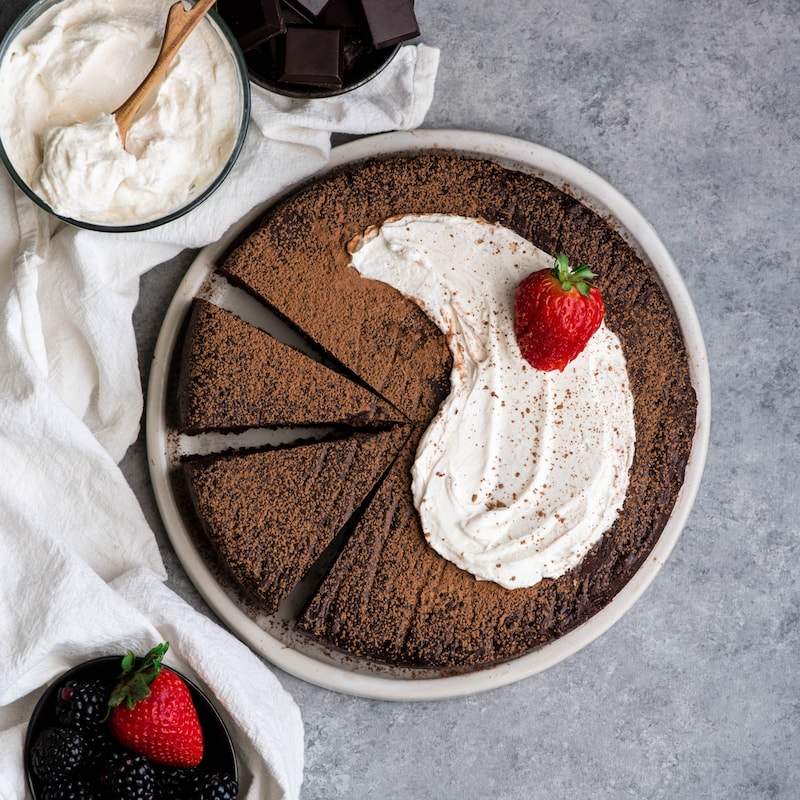 Overhead view of a Flourless Chocolate Cake, with two pieces cut, on a plate with whipped cream and a strawberry on top dusted with cocoa powder