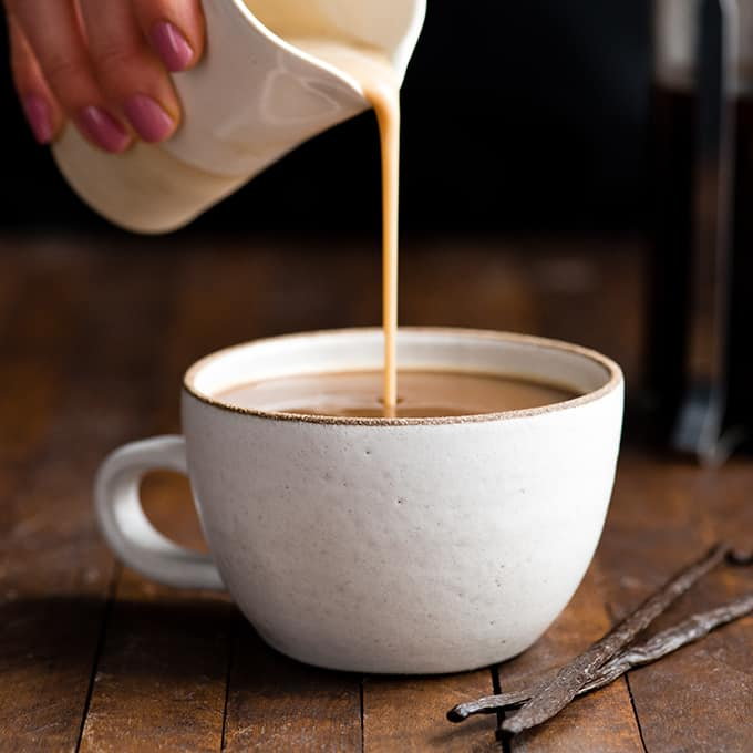 Front view of healthy coffee creamer being poured into a mug of coffee