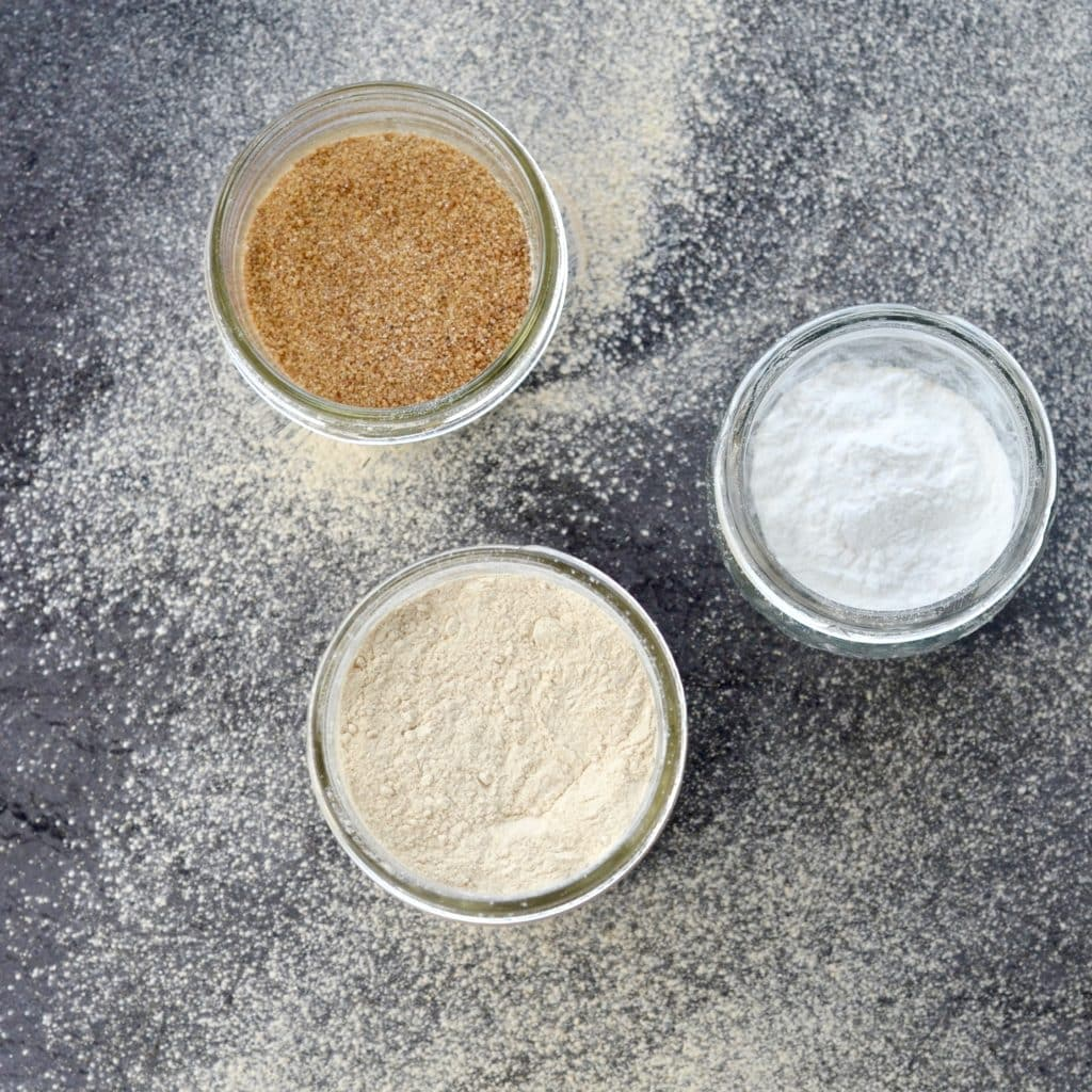 Overhead view of Homemade Paleo Powdered Sugar Recipe in a glass jar with two glass jars near it, one with coconut sugar and one with tapioca flour