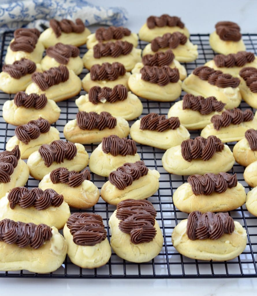 front view of a cooling rack full of 40 mini eclairs from the best eclairs recipe