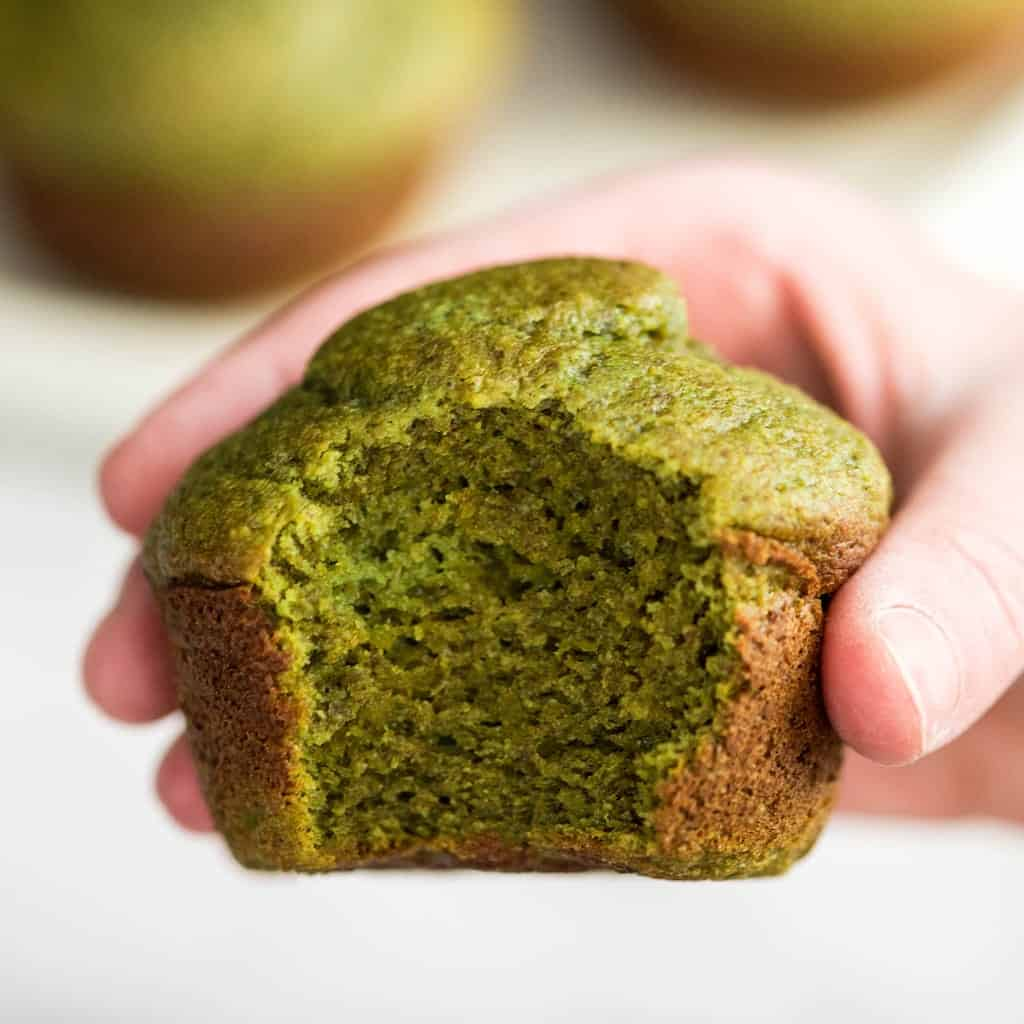 Up close front shot of a hand holding one spinach banana muffin with a bite taken out of it