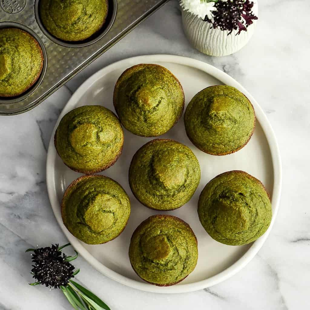 Overhead view of a round platter with 7 spinach banana muffins arranged in a circle on it with one in the middle and the muffin pan with two muffins next to it