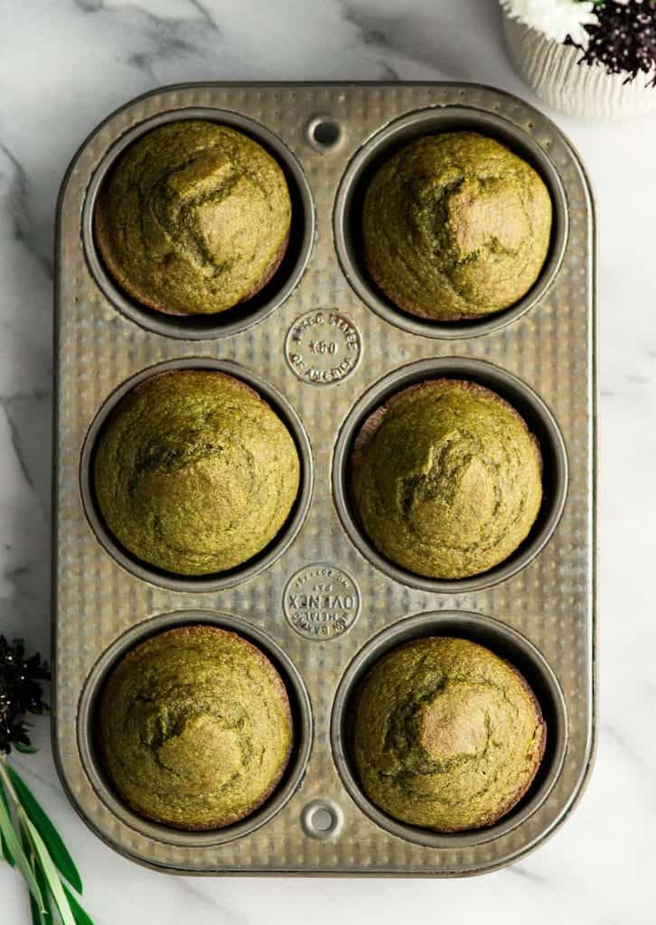 Overhead view of 8 spinach banana muffins in a muffin pan