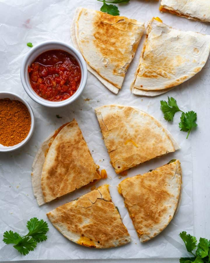 overhead photo of two chicken quesadillas, each cut into four triangular pieces.