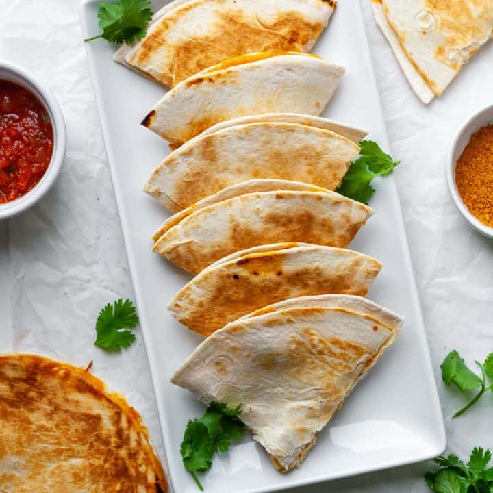 overhead view of 7 triangular pieces of chicken quesadilla in a line on a serving plate.