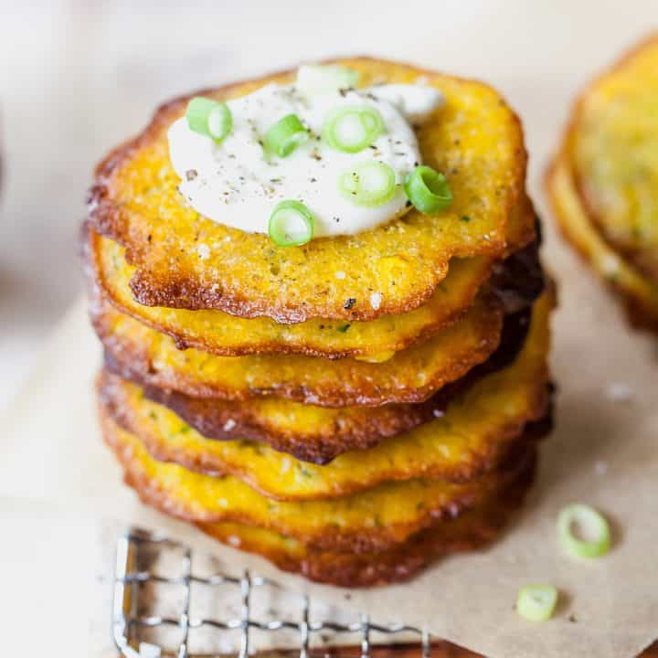 front view of a stack of 7 corn and zucchini fritters topped with sour cream