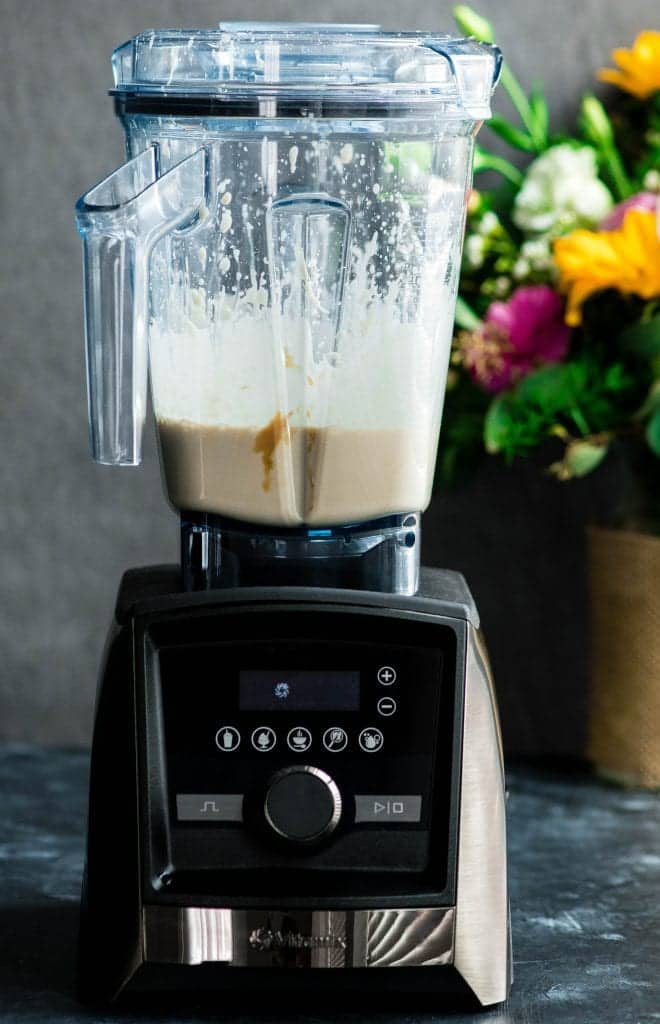 Front view of a Vitamix blender with the finished Paleo Vanilla Ice Cream mixture inside