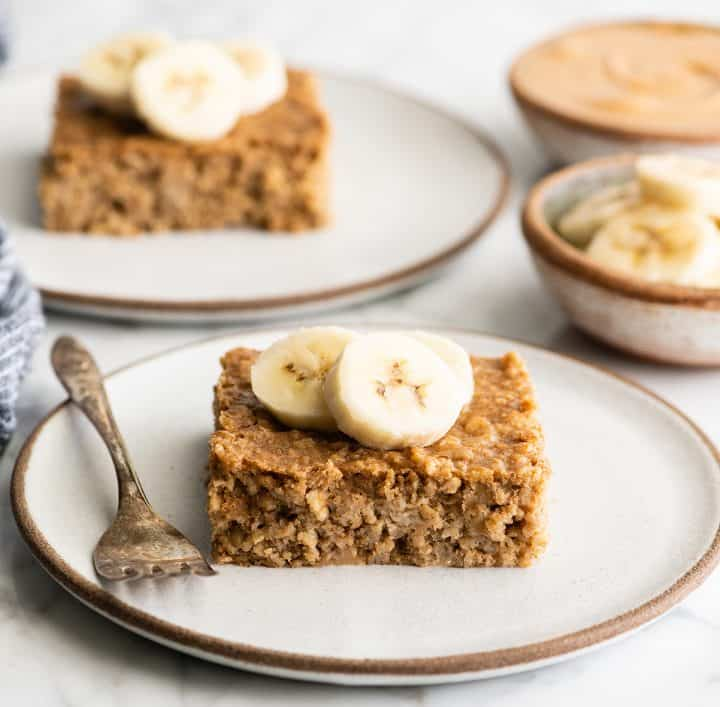 front view of a piece of peanut butter banana baked oatmeal on a plate with bananas on top