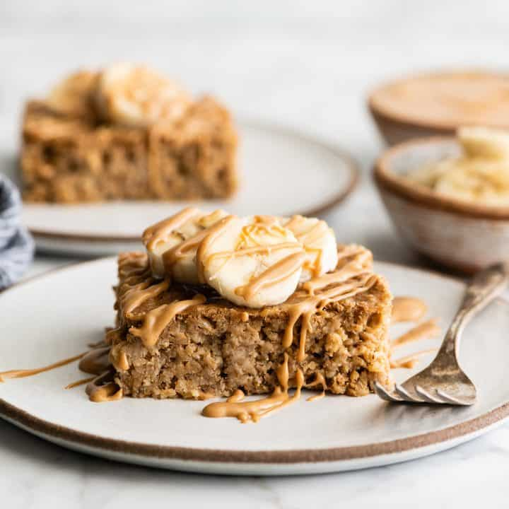 front view of a piece of peanut butter banana baked oatmeal on a plate with bananas on top and drizzled with peanut butter