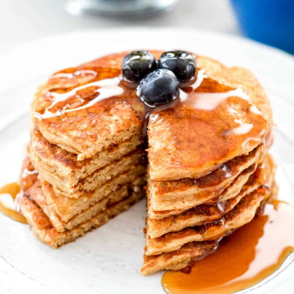 Front view of a stack of six gluten-free Greek Yogurt Pancakes with blueberries on top and a generous drizzle of maple syrup