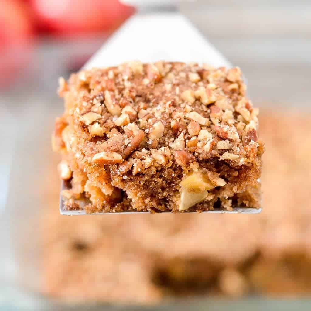 Overhead view of a piece of Paleo Apple Cake on a spatula being lifted out of the baking pan