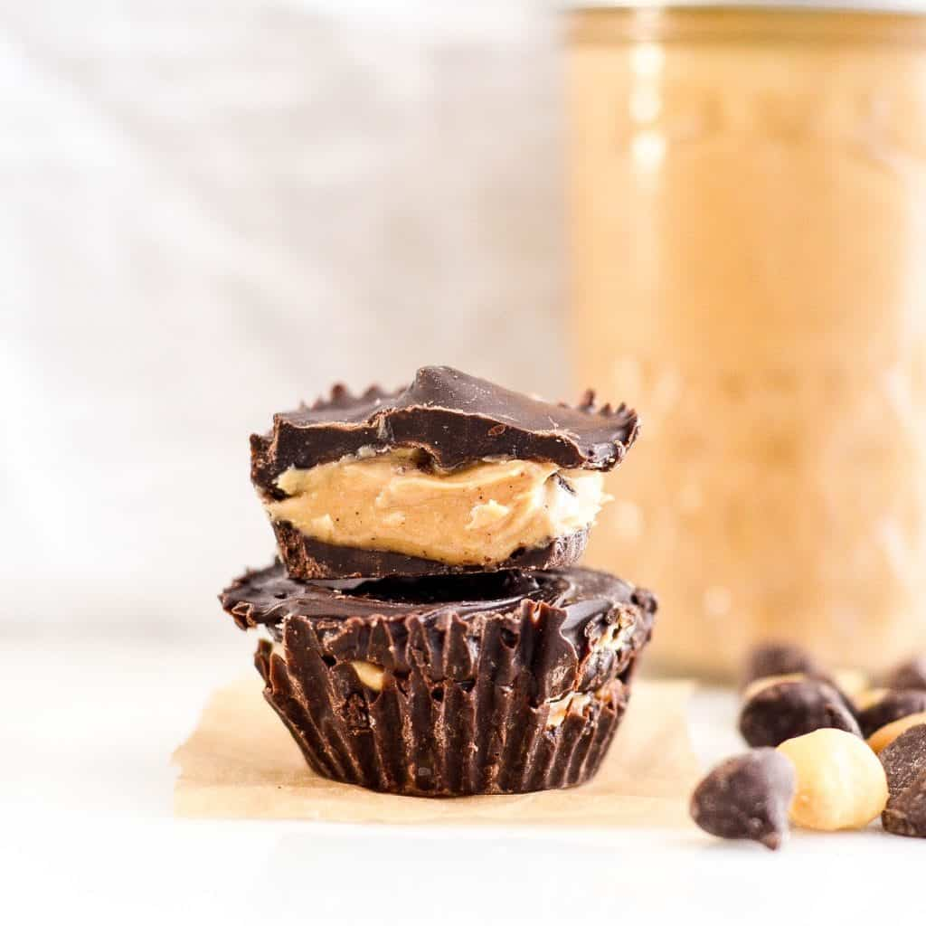 Front view of two Healthy Homemade Peanut Butter Cups stacked on each other. The top is cut in half with the inside showing