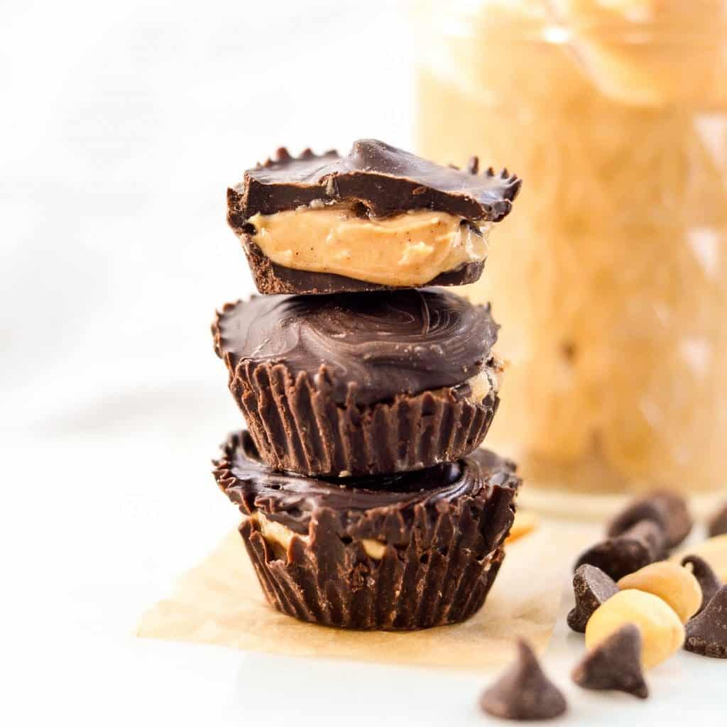 Front view of three Healthy Homemade Peanut Butter Cups stacked on each other, the top one is cut in half with the inside showing!