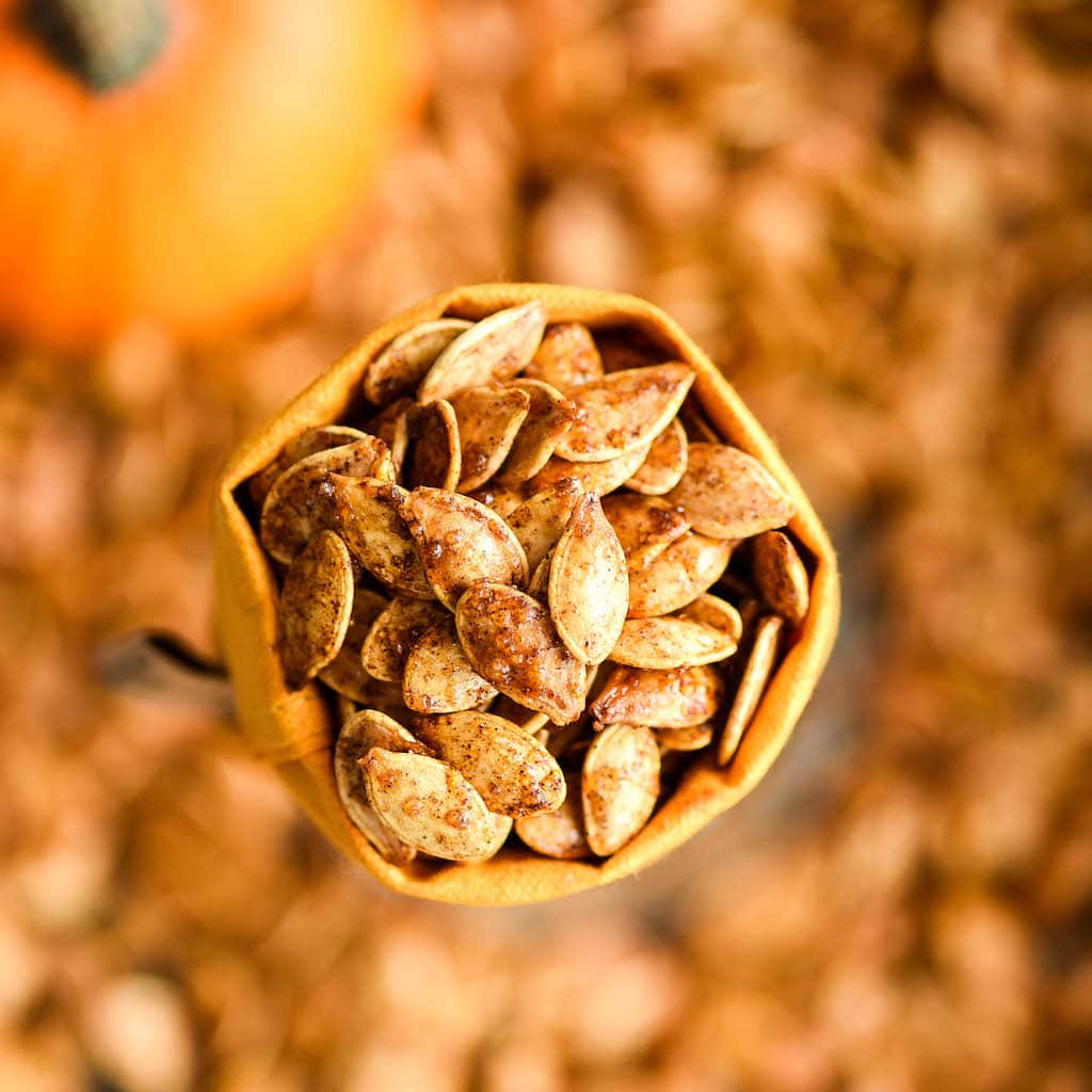 Overhead view of Homemade Cinnamon Sugar Pumpkin Seeds in a small bag with more roasted pumpkin seeds in the background