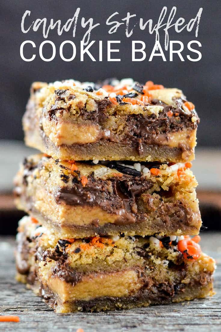 Candy Cookie Bars! Two layers of gooey chocolate chip cookie dough stuffed with the candy of your choice! The perfect dessert recipe to use up that Halloween Candy or adapt them for any holiday! #cookiebars #candycookiebars #chocolatechipcookiebars #cookies #chocolatechipcookies #dessert #recipe
